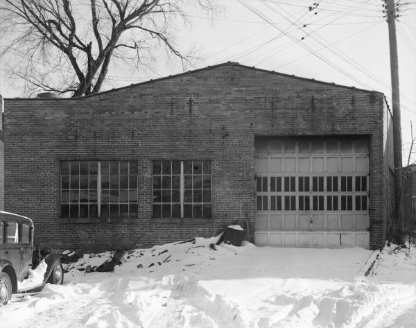 View of the exterior of the Schulz Garage, with two blocks of windows, and a large garage door. Snow is on the ground, and an automobile is parked near the building on the left. A power pole is next to the buildig on the right, and power lines are crisscrossing over the garage roof.