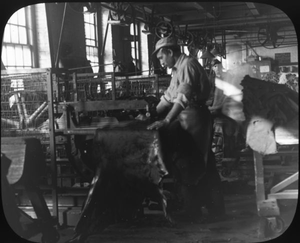 Interior view of the Pfister and Vogel Tannery, with a man working on leather at a machine.