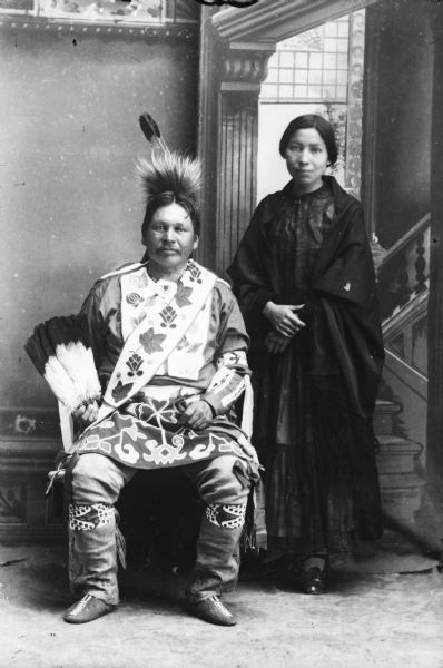 Studio portrait in front of a painted backdrop of Alex Lonetree, sitting and his wife, standing. They came to live with the Winnebagos after the last removal to Nebraska.