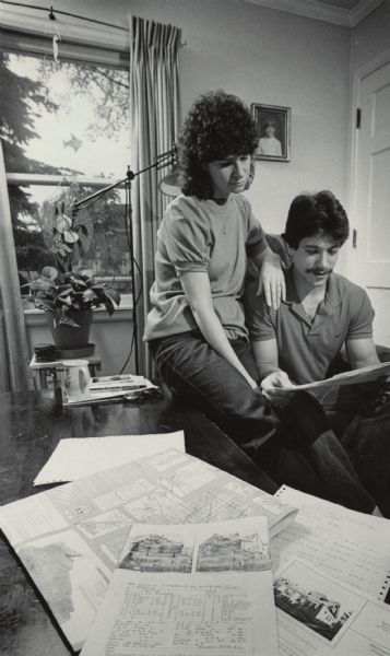 "A woman and a man are posing together in a room. The man is sitting in a chair, and the woman is sitting on the arm of the chair. On a table in the foreground are real estate listings. Caption reads: ""Mary and Mark Drews study the real estate listings."""