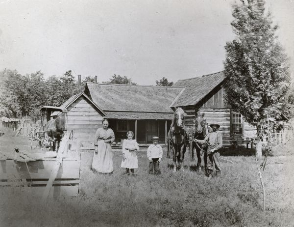 A man, his wife and their two children are posing in front of their farmstead. The man is holding a team of horses. Another horse pulling a buggy is in the background on the left.