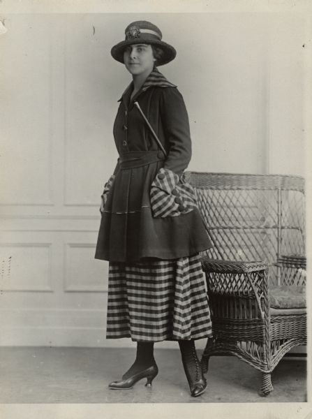"A woman is standing and posing near a wicker chair. She is wearing a hat, coat, skirt, and has a cane tucked under her arm. Caption reads: ""Smart hiking suit in dark green velour in combination of half inch check in green and grey."""