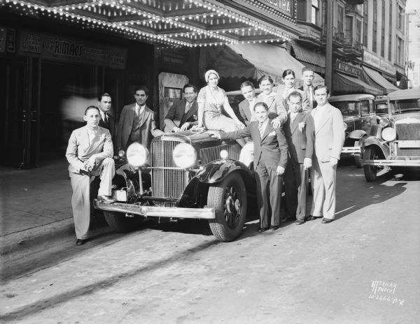 The Rimacs and their Havana Rumba Orchestra standing around a new Nash automobile, the Kenosha twin ignition six, Model 990, in front of the Orpheum Theatre, 216 State Street.