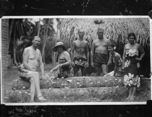Group portrait of Professor Ross and five friends in native dress in Tahiti. Two of the people are sitting on a stack of logs, with a cat sitting between them.